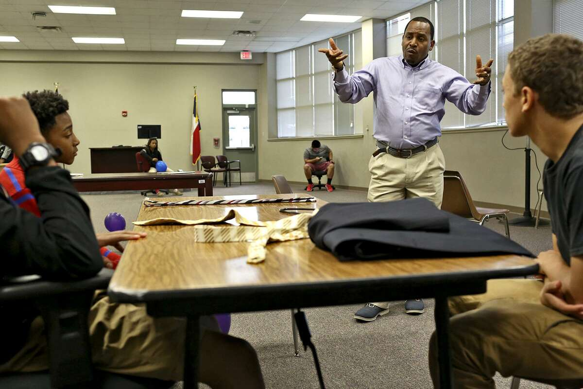 Walter Perry teaches boys how to interact in professional settings during SUIT UP!, a business and professional clothing program created by Perry, at the former Pfeiffer Elementary School on Oct. 25, 2016.