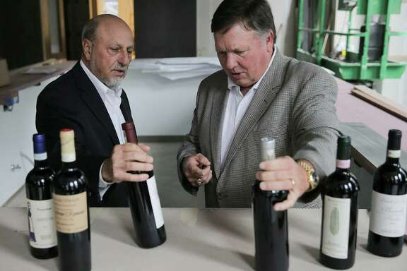 Rick Jamail, left, and Bill Floyd go over wine for their new high-end Italian restaurant downtown.