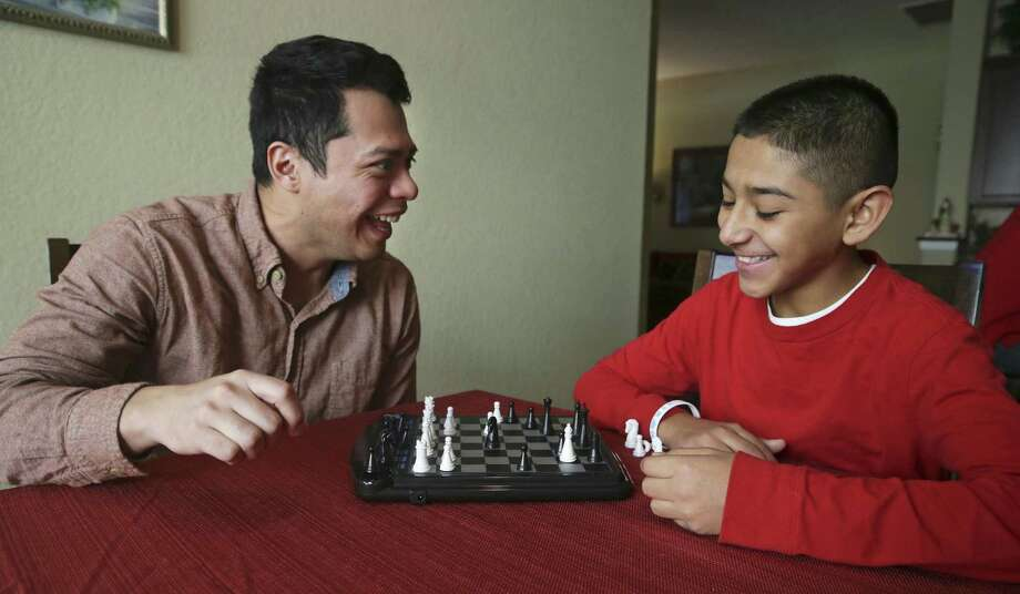 A game of chess brings smiles to Marcos Aceves as the Aceves family is visited by Big Brother Frank Herkules on Dec. 21. Photo: Tom Reel /San Antonio Express-News / 2016 SAN ANTONIO EXPRESS-NEWS
