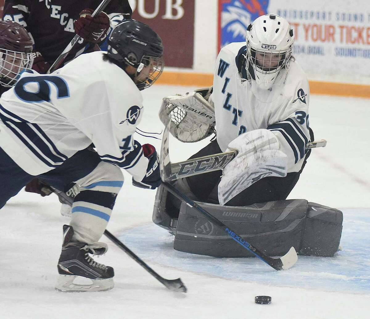 Wilton goalie Christopher Randolph, right, keeps an eye on the puck as his Warriors teammate Kevin Fung moves in to clear the puck during Monday afternoon's game against Bethel-Brookfield-Danbury at the Winter Garden Arena in Ridgefield.