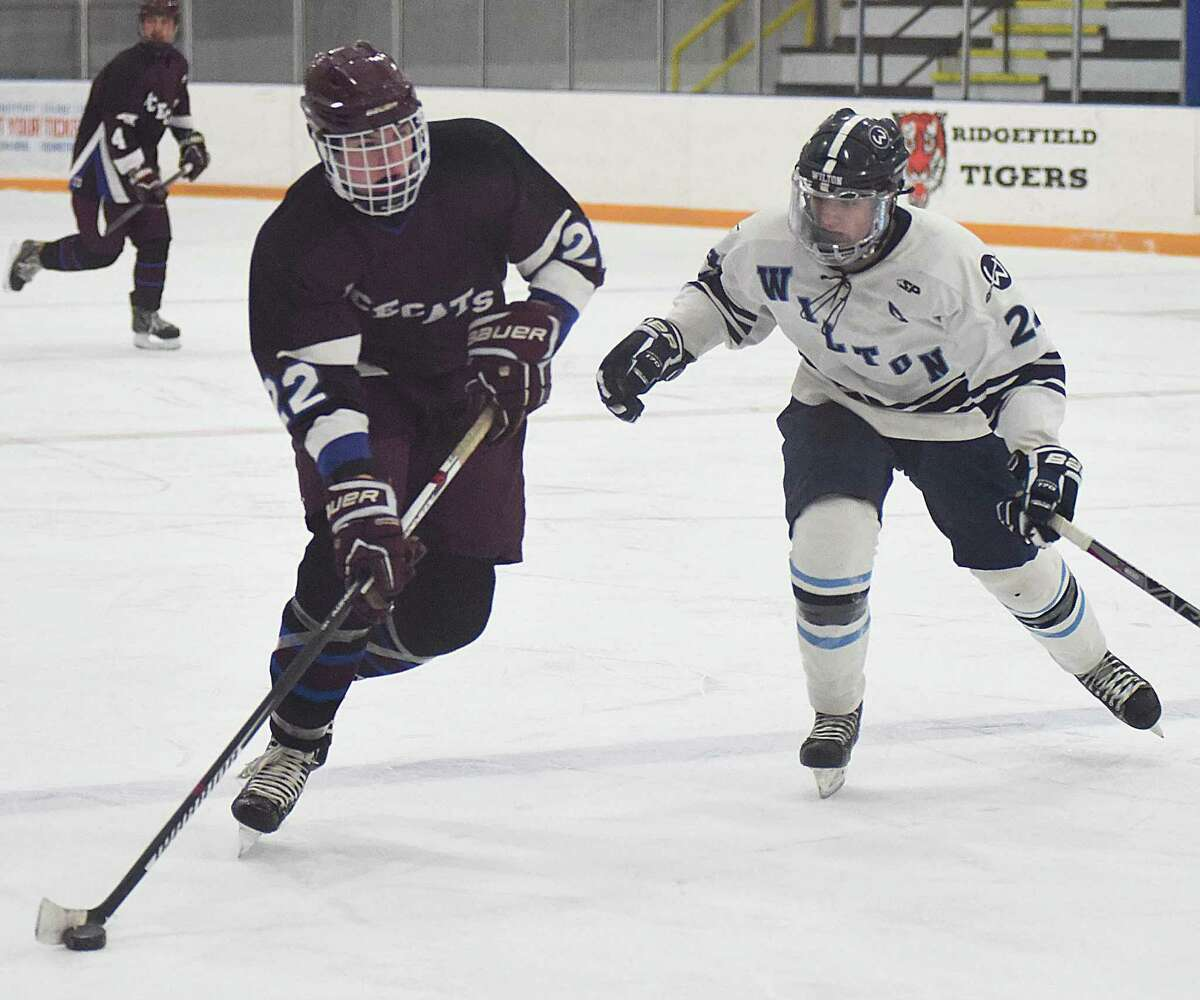 BBD skater Luke Newman, left, controls the puck as Wilton defender Alec Biegen moves in to defend during Monday's non-conference hockey game at the Winter Garden Arena in Ridgefield.