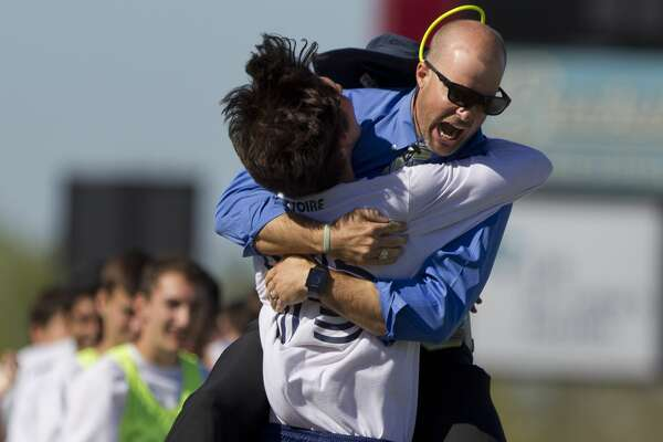 College Park head coach John Owens celebrates with Andrew Chodorow after Chodorow'sfirst period goal during a Region II-6A bi-district playoff game at Woodforest Bank Stadium Thursday. Westfield defeated College Park 3-2 in extra time.