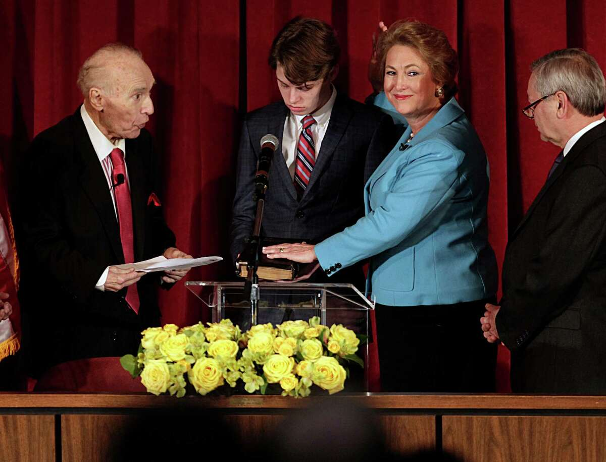 Former state Sen. Jack C. Ogg, left, administers the oath of office to daughter Kim Ogg, the county's new district attorney, as her son Jack Jordan assists on Monday.