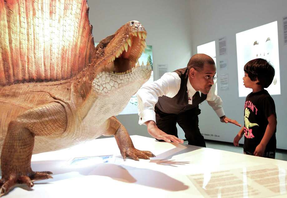 """""""Jurassic"""" James Washington, perhaps the Houston Museum of Natural Science's most popular tour guide, demonstrates the difference between a lizard and a dinosaur to Ajay Selva, 4.  Photo: Elizabeth Conley, Staff / © 2016 Houston Chronicle"""