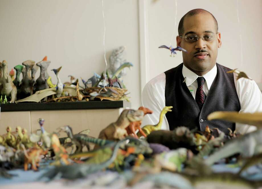 James Washingtondisplays his collection of dinosaur toys and models that are separated by geological time periods.