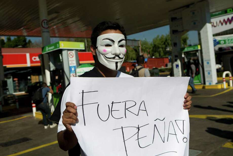 """A protester with a Guy Fawkes mask holds a sign Monday that says in Spanish """"Peña Out!"""" as people angry over gasoline prices under President Enrique Peña Nieto's government block a gas station in Mexico City. Photo: Rebecca Blackwell, STF / Copyright 2017 The Associated Press. All rights reserved."""