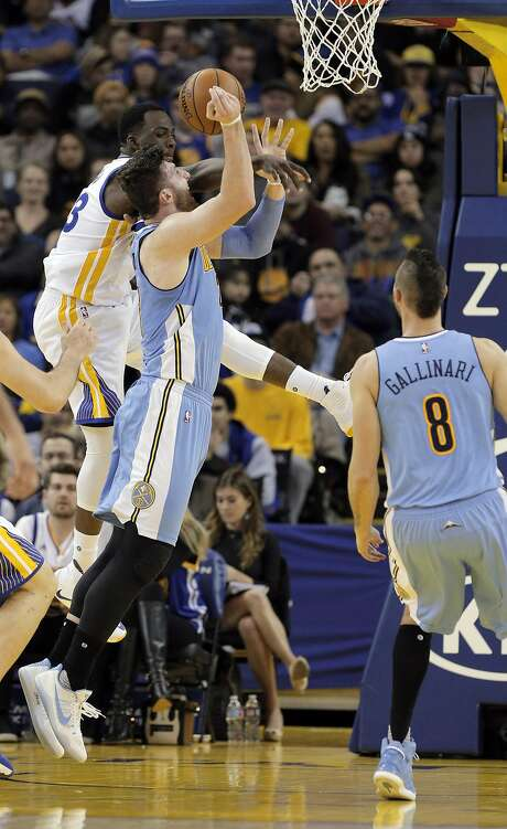 Draymond Green (23) leaps up to block a shot by Jusuf Nurkic (23) but fouled him in the first half as the Golden State Warriors played the Denver Nuggets at Oracle Arena in Oakland, Calif., on Monday, January 2, 2017. Photo: Carlos Avila Gonzalez, The Chronicle