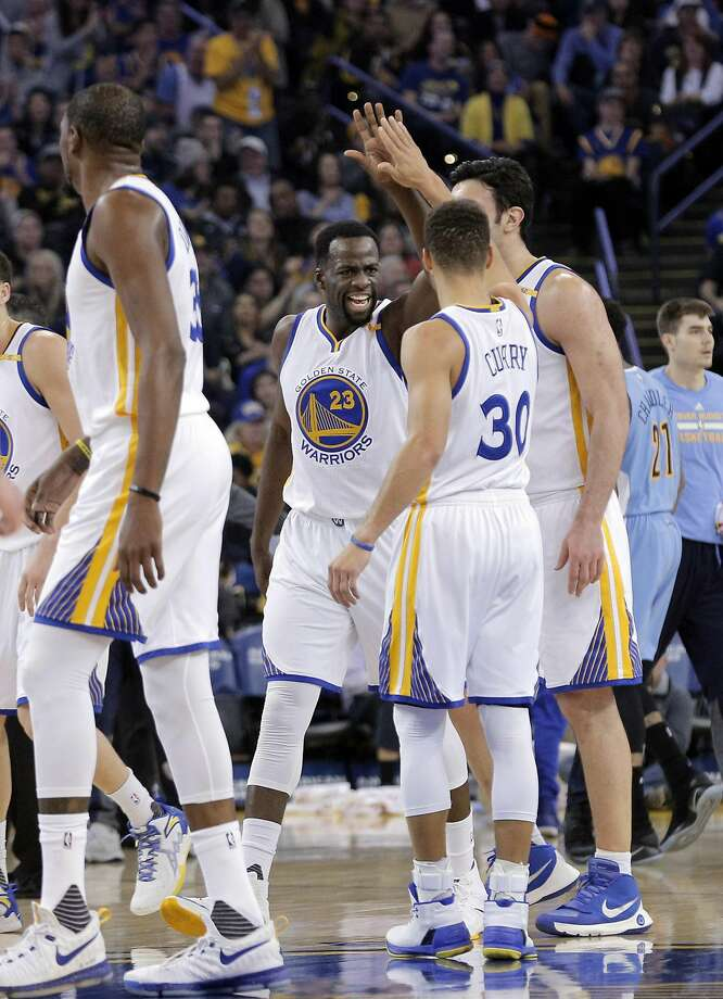 The Warriors high five during a time out in the first half as the Golden State Warriors played the Denver Nuggets at Oracle Arena in Oakland, Calif., on Monday, January 2, 2017. Photo: Carlos Avila Gonzalez, The Chronicle