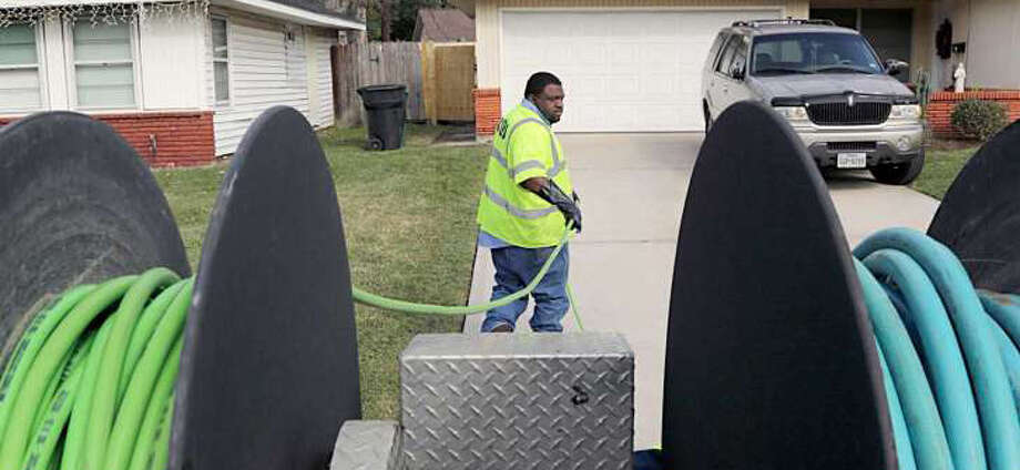 A Houston Public Works employee works to clear a resident's blocked sewer line. Photo: Crop For Newsletter