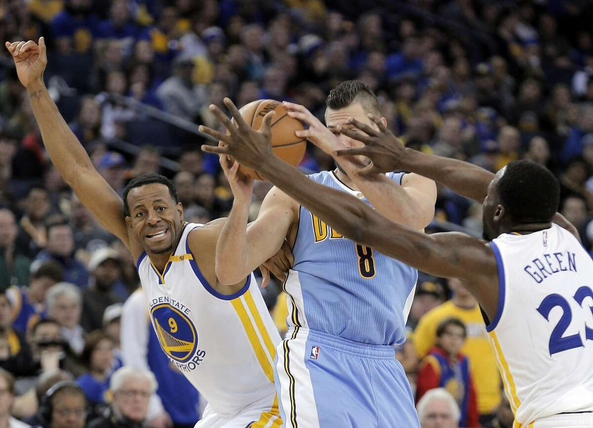 Andre Iguodala (9) and Draymond Green (23) swarm Danilo Gallinari (8) in the second half as the Golden State Warriors played the Denver Nuggets at Oracle Arena in Oakland, Calif., on Monday, January 2, 2017.