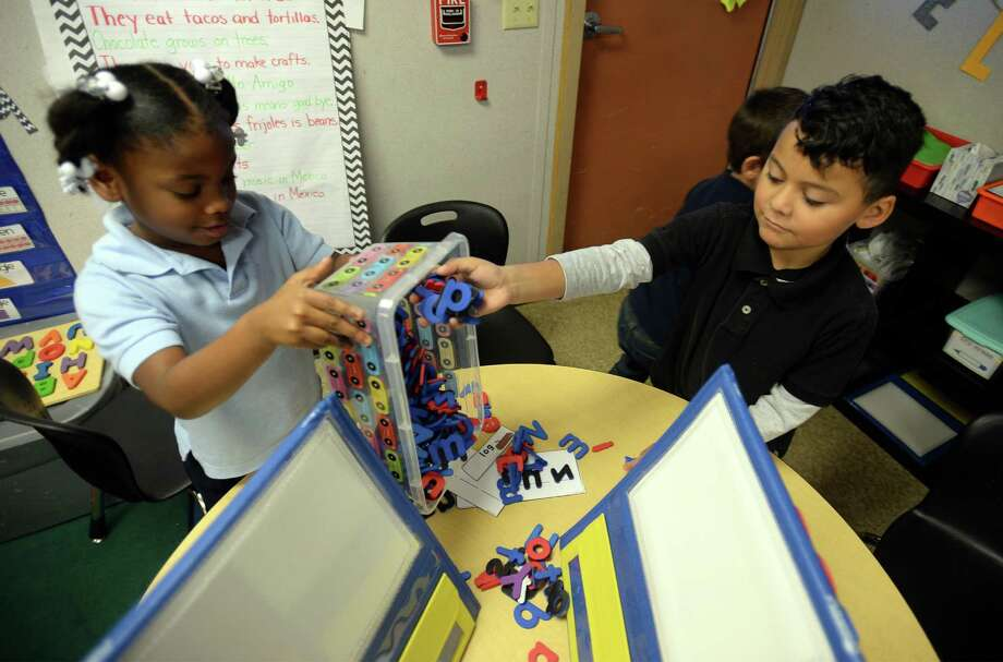 Malachi Rimirez puts magnetic alphabet letters in a container while Kamyle Martin dumps them out at 	Dowling Elementary on Friday. The letters are part of a learning tool that was purchased by the student's teacher Marissa Phillips who used a crowdfunding website to raise money for school supplies.  Photo taken Friday, December 09, 2016 Guiseppe Barranco/The Enterprise Photo: Guiseppe Barranco, Photo Editor