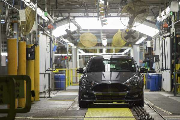 Ford Focus vehicles are assembled at the Ford Michigan Assembly Plant in Wayne, Michigan. The second-largest U.S. automaker will build two products at a factory in Wayne, Michigan, protecting about 3,500 jobs. It also announced it will scrap plans to build a $1.6 billion plant in Mexico.