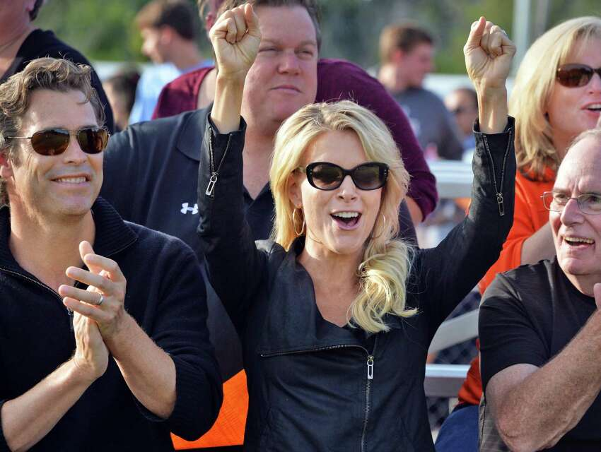 BCS class of ?'88 grad Megyn Kelly of Fox News cheers a touchdown by her team before a halftime Hall of Fame induction ceremony at Bethlehem Central High School Saturday Sept. 26, 2015 in Bethlehem, NY. At left is Megyn's husband, novelist Doug Brunt. (John Carl D'Annibale / Times Union)