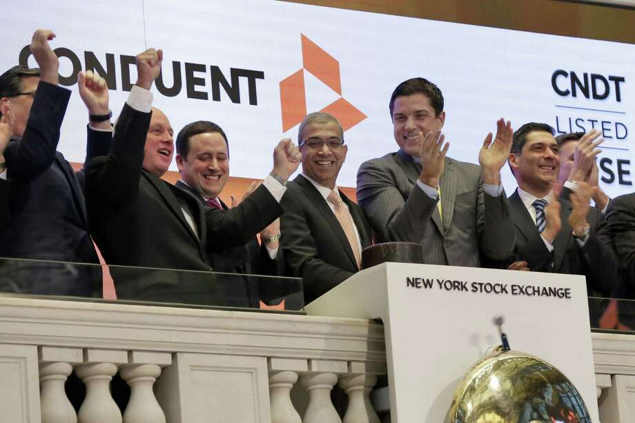 Conduent CEO Ashok Vemuri, center, is applauded as he rings opening bell of the New York Stock Exchange, to mark his company's spinoff from Xerox, Tuesday, Jan. 3, 2017. The stock market opened the year on a strong note, led by big gains in banks and energy companies. (AP Photo/Richard Drew)) Photo: Richard Drew / Associated Press / AP
