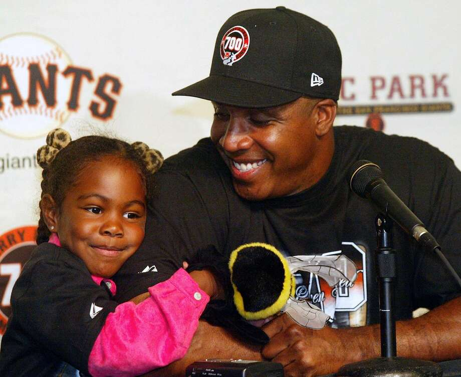 San Francisco Giants' Barry Bonds, right, is hugged by his daughter, Aisha, 5, at a news conference after hitting his 700th career home run in the Giants' 4-1 win over the San Diego Padres, Friday, Sept. 17, 2004, in San Francisco.  Photo: GEORGE NIKITIN, AP