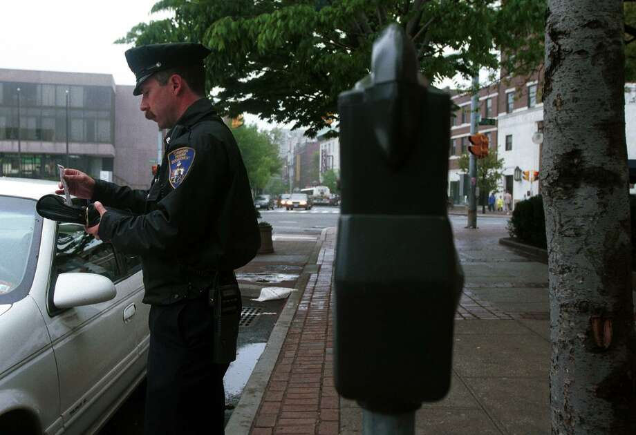This file photo shows a parking enforcement officer preparing to ticket a car parked on Bedford Street. Photo: File Photo /Hearst Connecticut Media
