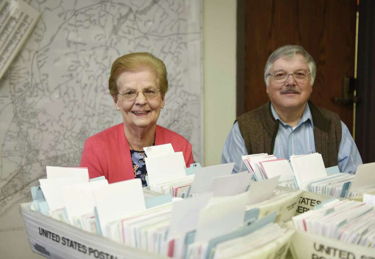 Longtime Democratic Registrar of Voters Sharon Vecchiolla and her successor Michael Aurelia pose beside voting documents in the registrar's office at Town Hall in Greenwich.