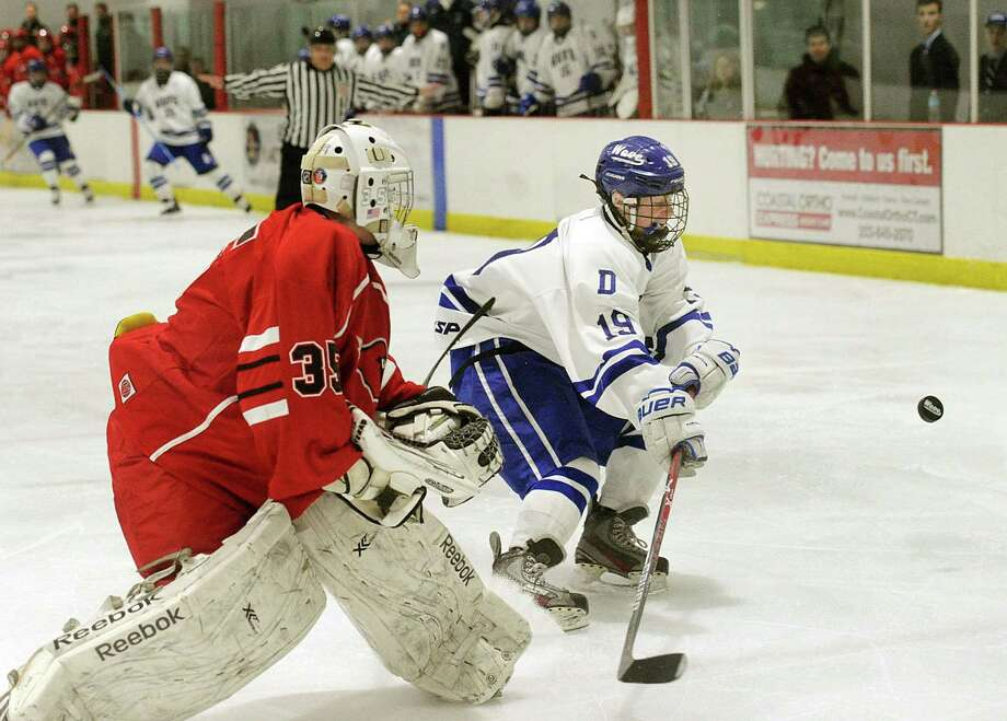 Ryan Niederreither (19) of Darien goes after the puck off his own rebounded shot that was initially blocked by Greenwich goalie Dylan Dreher (35), left, on Thursday. Photo: Bob Luckey Jr. / Hearst Connecticut Media / Greenwich Time