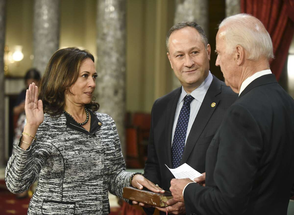 Vice President Joe Biden administers the Senate oath of office to Sen. Kamala Harris, D-Calif., as her husband Douglas Emhoff, holds the Bible during a a mock swearing in ceremony in the Old Senate Chamber on Capitol Hill in Washington, Tuesday, Jan. 3, 2017, as the 115th Congress begins. (AP Photo/Kevin Wolf)