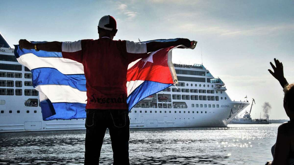 A man waves a Cuban flag at the Malecon waterfront as the first U.S.-to-Cuba cruise ship to arrive in the island nation in decades glides into the port of Havana, on May 2, 2016. The first US cruise ship bound for Cuba in half a century, the Adonia -- a vessel from the Carnival cruise's Fathom line -- set sail from Florida marking a new milestone in the rapprochement between Washington and Havana. The ship -- with 700 passengers aboard -- departed from Miami, the heart of the Cuban diaspora in the United States.