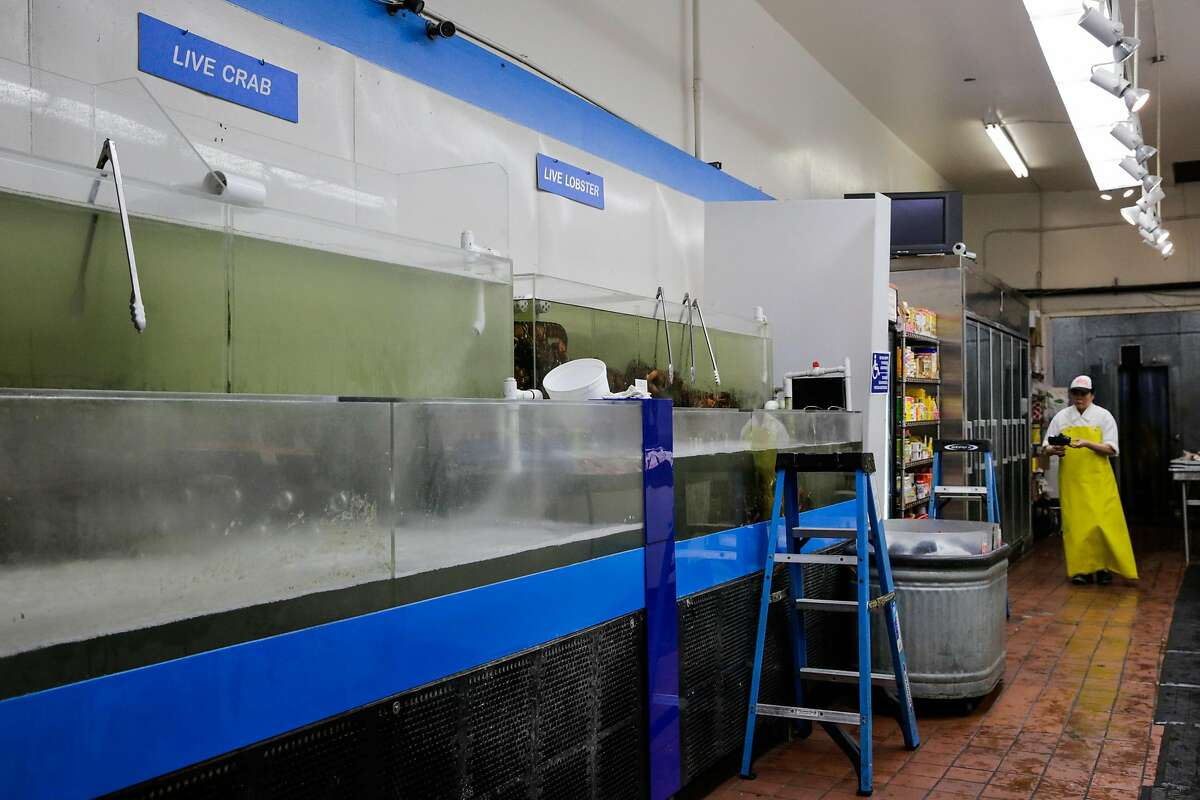 An empty crab tank is seen while managaer Man Lai (right) works at Sun Fat Seafood Company, a seafood market in the Mission district in San Francisco, Calif., on Tuesday, Jan. 3, 2017.