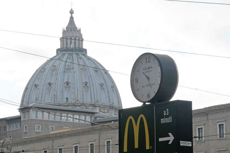 A sign showing the direction of a McDonald restaurant is seen with the cupola of St Peter's basilica in the background Tuesday. The US fast-food chain opened a restaurant in a Vatican-owned building despite protests. Photo: Tiziana Fabi /AFP /Getty Images / AFP or licensors