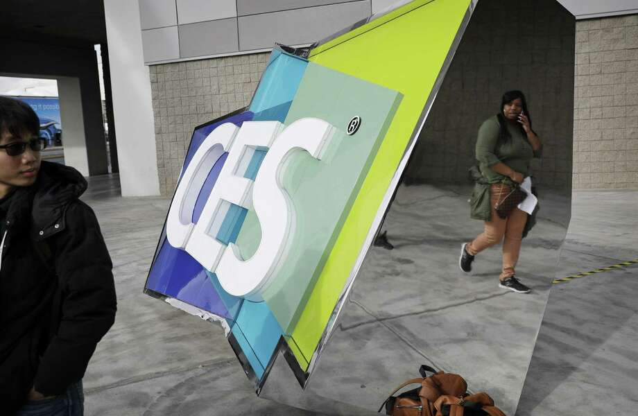People walk by a sign during setup Tuesday for the annual CES tech show. Photo: John Locher /Associated Press / Copyright 2017 The Associated Press. All rights reserved.