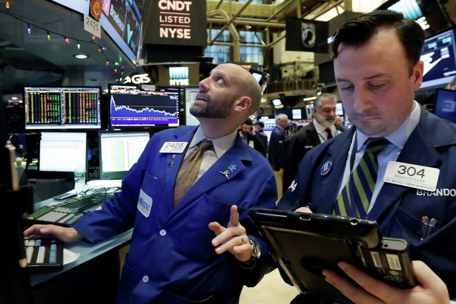 Specialist Meric Greenbaum, left, works at his post on the floor of the New York Stock Exchange, Tuesday, Jan. 3, 2017. The stock market opened the year on a strong note, led by big gains in banks and energy companies. (AP Photo/Richard Drew)) Photo: Richard Drew, STF / AP