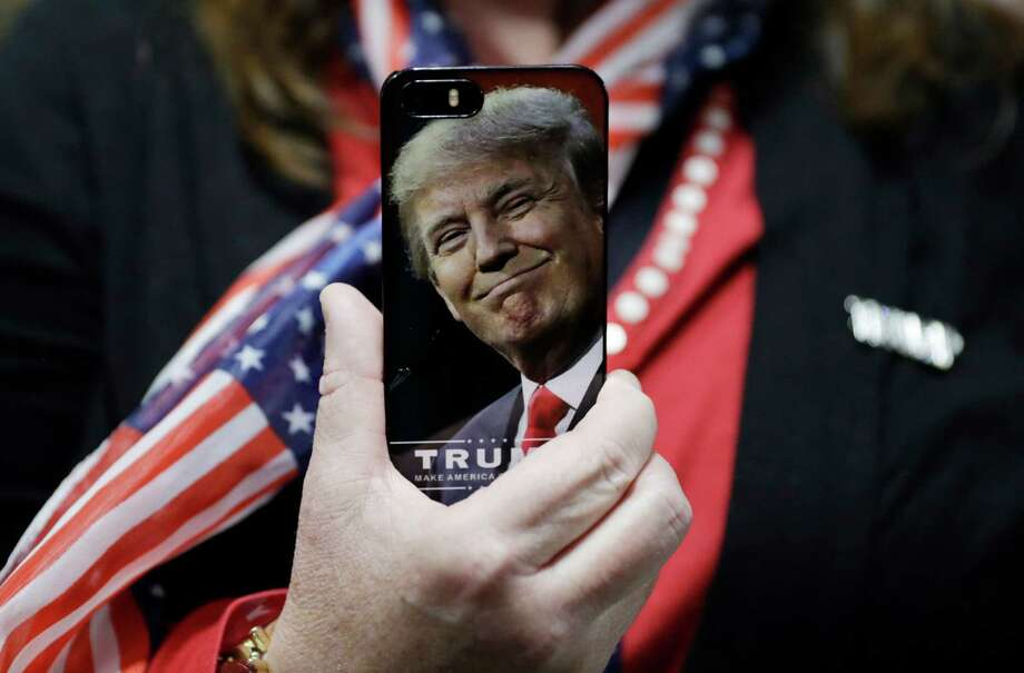 FILE - In this Thursday, Sept. 29, 2016, file photo, a woman holds up her cell phone before a rally with then presidential candidate Donald Trump in Bedford, N.H. President-elect Trump tweeted Tuesday that North Korea won't develop a nuclear weapon capable of reaching parts of the United States, but it's possible it already has. After five atomic test explosions and a rising number of ballistic missile test launches, many experts believe that North Korea can arm short- and mid-range missiles with warheads that put Guam at risk. (AP Photo/John Locher, File) Photo: John Locher, STF / Copyright 2016 The Associated Press. All rights reserved.