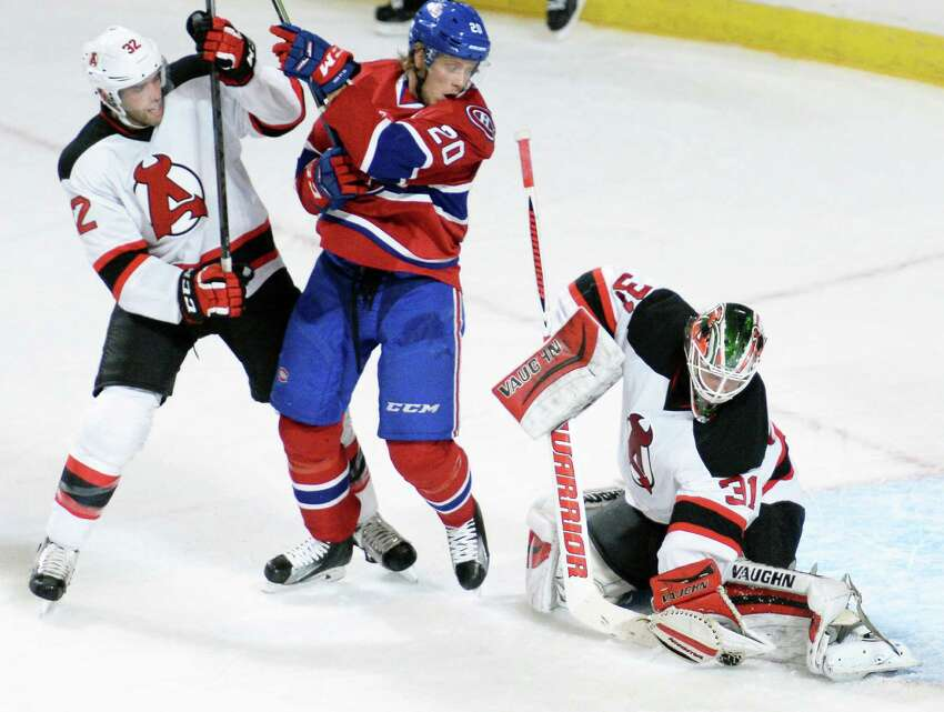 Albany Devils's #32 Brandon Gormley, left, and St. John's IceCaps' #20 Jacob de la Rose look on as goalie Scott Wedgewood traps the puck during Saturday's home opener at the Times Union Center Oct. 15, 2016 in Albany, NY. (John Carl D'Annibale / Times Union) ORG XMIT: MER2016101520305849