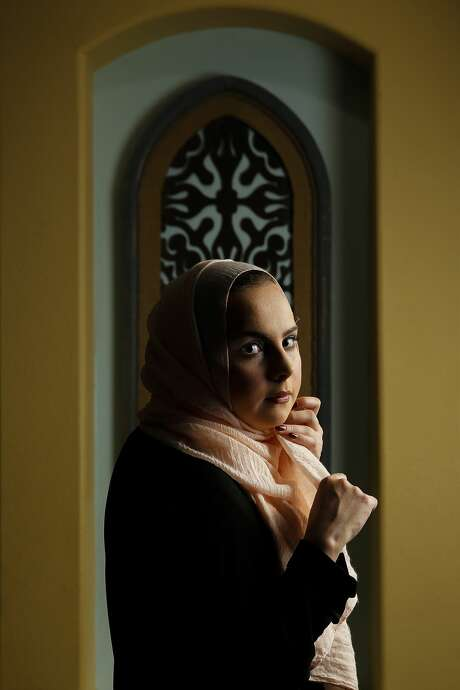 """Shifa Abuzaid, 21, adjusts her hijab for a portrait in her home Tuesday, Jan. 3, 2017 in Richmond. Abuzaid was out in the Sugar Land Town Center with her siblings and cousins when a man passing by them called them a """"bunch of terrorists"""" and shoved Abuzaid's younger brother after being confronted. A video of the incident that Abuzaid posted now has over 350,000 views in the time since she uploaded it to Facebook to warn others after Sugar Land police declined to file a report after the incident. ( Michael Ciaglo / Houston Chronicle ) Photo: Michael Ciaglo/Houston Chronicle"""