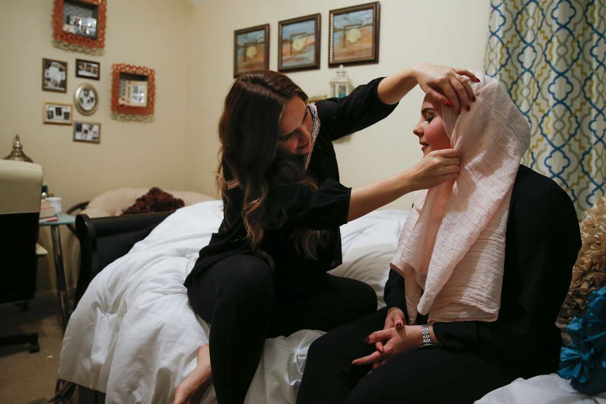 """Janan Abuzaid, 20, left, adjusts the hijab of her sister, Shifa Abuzaid, 21, for a portrait on Shifa's bed in their home Tuesday, Jan. 3, 2017 in Richmond. Shifa was out in the Sugar Land Town Center with her sister, brother and cousins when a man passing by them called them a """"bunch of terrorists"""" and shoved Shifa's younger brother after being confronted. A video of the incident that Shifa posted now has over 350,000 views in the time since she uploaded it to Facebook to warn others after Sugar Land police declined to file a report after the incident. ( Michael Ciaglo / Houston Chronicle )"""