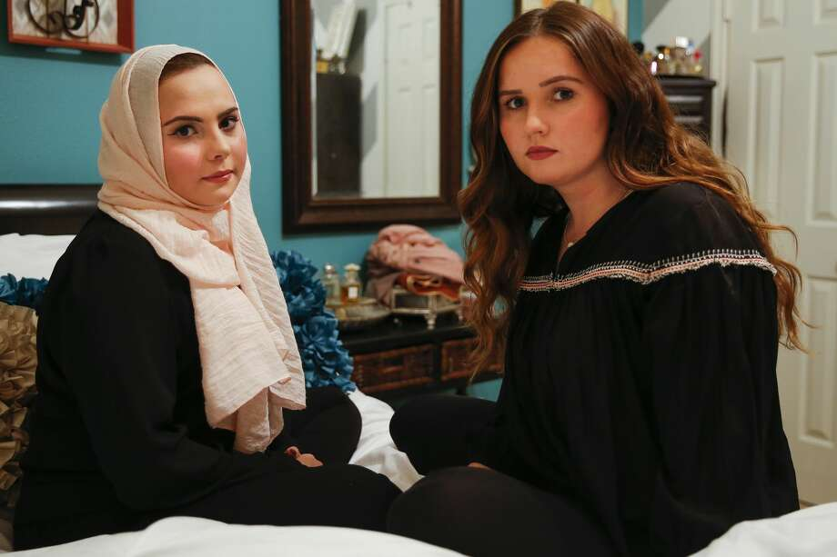 """Sisters Shifa Abuzaid, 21, left, and Janan Abuzaid, 20, sit on Shifa's bed for a portrait in their home Tuesday, Jan. 3, 2017 in Richmond. Shifa was out in the Sugar Land Town Center with her sister, brother and cousins when a man passing by them called them a """"bunch of terrorists"""" and shoved Shifa's younger brother after being confronted. A video of the incident that Shifa posted now has over 350,000 views in the time since she uploaded it to Facebook to warn others after Sugar Land police declined to file a report after the incident. ( Michael Ciaglo / Houston Chronicle ) Photo: Michael Ciaglo/Houston Chronicle"""