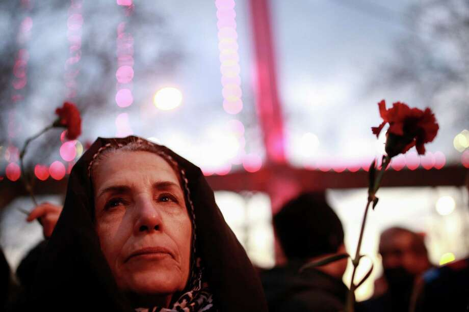 """A woman stands with others at the scene of the New Year's Day attack, in Istanbul.  The Islamic State group claimed responsibility, saying a """"soldier of the caliphate"""" had carried out the mass shooting. Photo: Emrah Gurel, STR / Copyright 2017 The Associated Press. All rights reserved."""