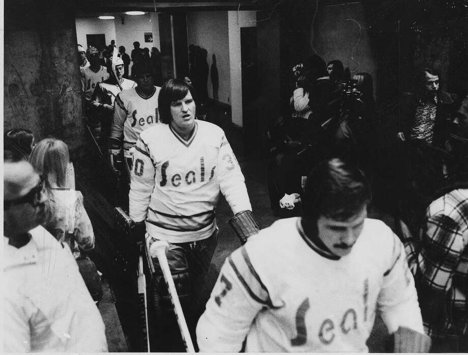 Goalies Gary Simmons, center, and Gilles Meloche, right, lead the team onto the ice at the Oakland Arena. Photo: Jerry Telfer, San Francisco Chronicle