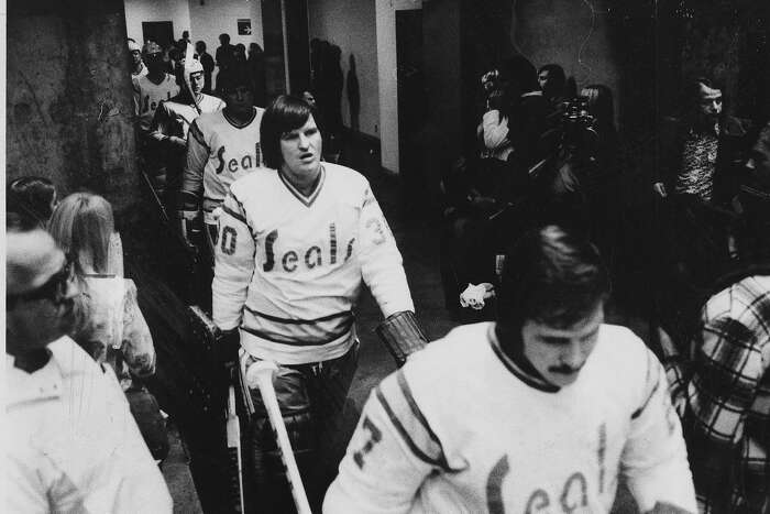 California Golden Seals head for the Ice at the Oakland Arena leading the way are Gary Simmons (l) and Gilles Miloche, Photo ran 12/20/1974, p. 63