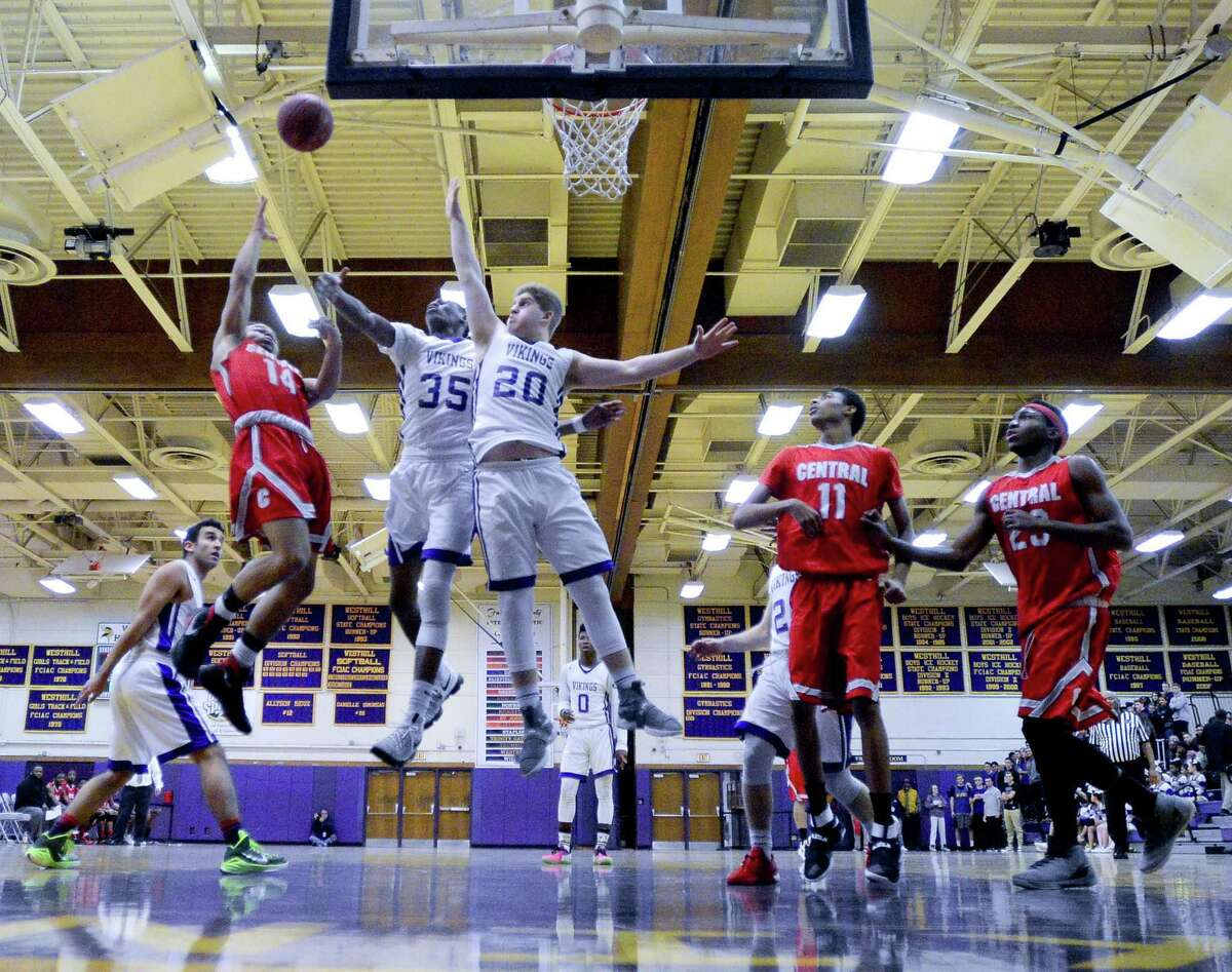 Central Wilner Agramonte throws up a shot in the paint under pressure from Westhill J'Ani Grahamin and Sam Lombino in the first half of a boys basketball game at Westhill High School on Jan. 3, 2017. Central DJ Fulton and Rajeeve Walker, at right, look for the rebound.