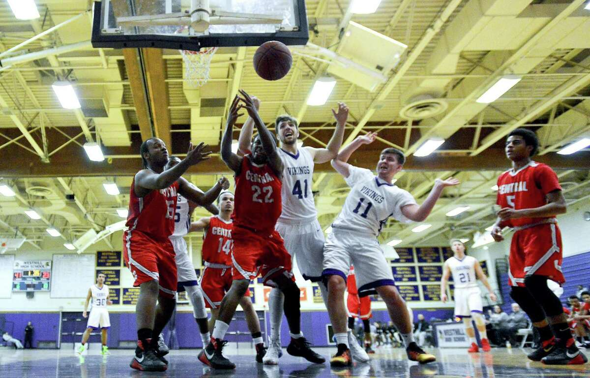 Central Raquan Rilley amd Westhill Hunter Semmel battle for a loose ball with Central Dashon Riley, at left, and Westhill Jake Dardis, at right, in a boys basketball game at Westhill High School on Jan. 3, 2017.