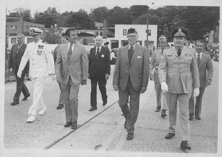 Westport's late First Selectman, Herb Baldwin (in glasses), John Cabot Lodge (in U.S. Navy uniform), Congressman Stuart McKinney, Merald Lue (middle of second row), Cliff Mills (right front) walk on the State Street Bridge (now Ruth Steinhaus Cohen Bridge) going east. The photograph dates back to in the 1950s and was probably taken on Memorial Day. Photo courtesy of the Westport Historical Society. Photo: Contributed Photo, Contributed Photo Courtesy Of Westport Historical Society / Westport News