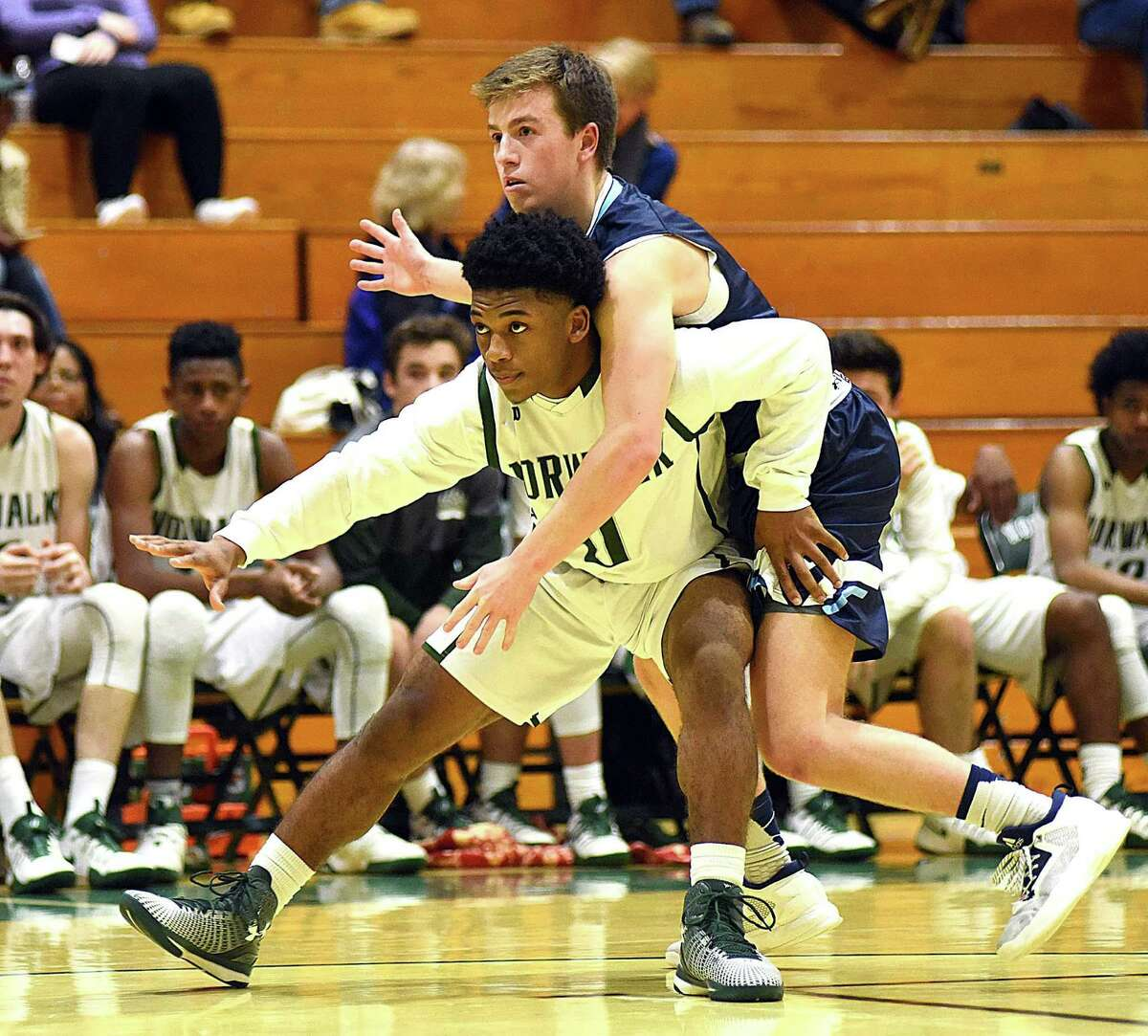 Norwalk's Deandre Russell, front, tries to hold off Wilton's Sean Breslin as the two battle for position on an inbounds pass during Tuesday's FCIAC boys basketball game at Scarso Gym in Norwalk. Wilton coasted to a 74-34 win over the Bears.