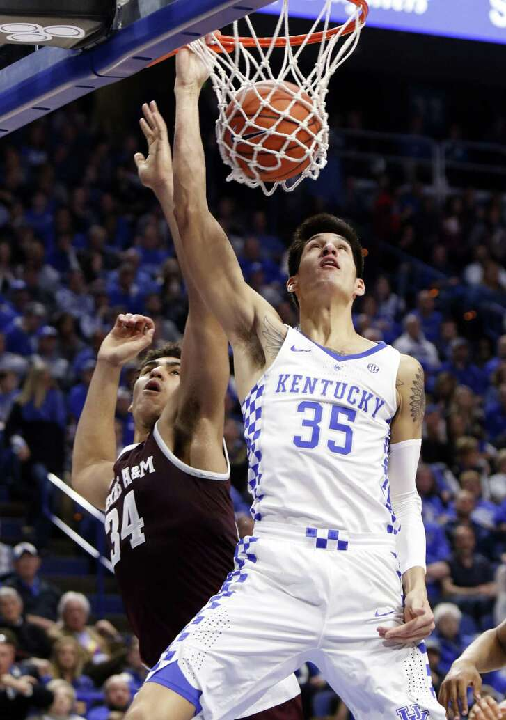 Kentucky's Derek Willis dunks while defended by Texas A&M's Tyler Davis during the first half of the Wildcats' blowout victory in Lexington. Kentucky forced 25 turnovers and broke 100 points for the second time in four games.