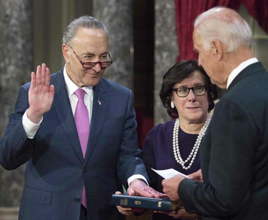 US Senator Charles Schumer (D-NY), US Vice-President Joe Biden(R) and Iris Schumer are seen during a reenacted swearing-in on January 3, 2017, in the Old Senate Chamber, on Capitol Hill, in Washington, DC. / AFP PHOTO / PAUL J. RICHARDSPAUL J. RICHARDS/AFP/Getty Images ORG XMIT: Vice Pres Photo: PAUL J. RICHARDS / AFP or licensors