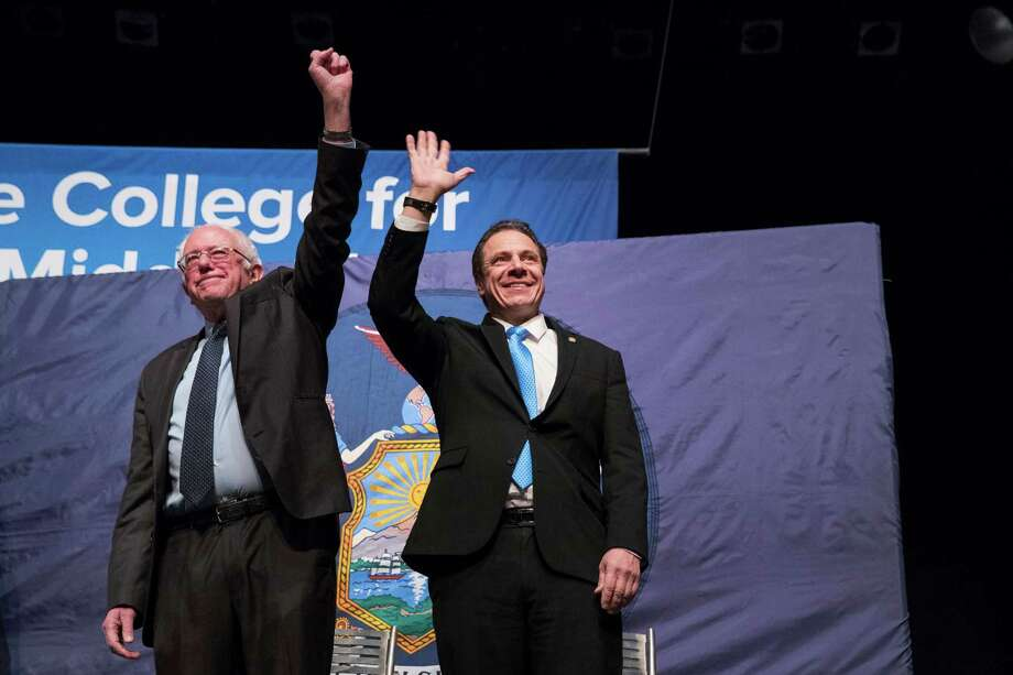New York Gov. Andrew Cuomo, right and Vermont Sen. Bernie Sanders wave at the audience as they arrive onstage at an event at LaGuardia Community College, Tuesday, Jan. 3, 2017, in New York. Gov. Cuomo announced a proposal for free tuition at state colleges to hundreds of thousands of low- and middle income residents. Under the governor's plan, which requires legislative approval, any college student accepted to a New York public university or two-year community college is eligible, provided their family earns less than $125,000. (AP Photo/Mary Altaffer) ORG XMIT: NYMA101 Photo: Mary Altaffer / Copyright 2017 The Associated Press. All rights reserved.