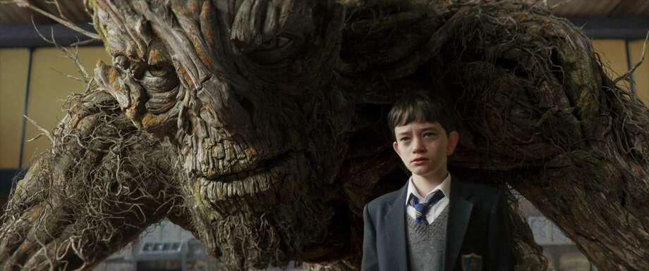 "Conor, played by Lewis MacDougall, is shadowed by The Monster, performed and voiced by Liam Neeson, in the new film ""A Monster Calls.""  Credit: Focus Features Photo: Focus Features / Online_yes"