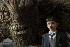 """Conor, played by Lewis MacDougall, is shadowed by The Monster, performed and voiced by Liam Neeson, in the new film """"A Monster Calls.""""  Credit: Focus Features"""
