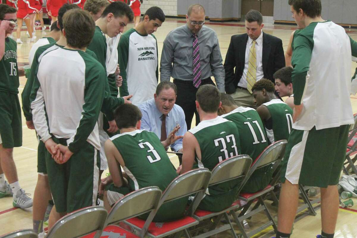 New Milford coach Al Tolomeo talks to the team during a time out.