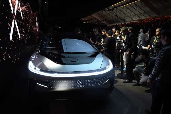 Attendees look at Faraday Future's FF 91 prototype electric crossover vehicle after it was unveiled during a press event for CES 2017 at The Pavilions at Las Vegas Market on January 3, 2017 in Las Vegas. The 1,050-horsepower FF 91 features autonomous driving with 3D lidar and can go from 0 to 60 mph in 2.39 seconds. CES, the world's largest annual consumer technology trade show, runs from January 5-8 and is expected to feature 3,800 exhibitors showing off their latest products and services to more than 165,000 attendees.