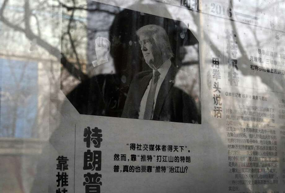 "A man reading a newspaper posted on a public newspaper bulletin board is reflected on a glass as a photo of U.S. President-elect Donald Trump is published on a Chinese newspaper with an article that reads ""Trump uses fist to talk"" in Beijing, Tuesday, Jan. 3, 2017. A state-run Chinese tabloid says Trump is ""pandering to 'irresponsible' attitudes"" after he accused China of not stepping in to curtail the North Korean nuclear program. (AP Photo/Andy Wong) Photo: Andy Wong, STF / Associated Press / Copyright 2017 The Associated Press. All rights reserved."