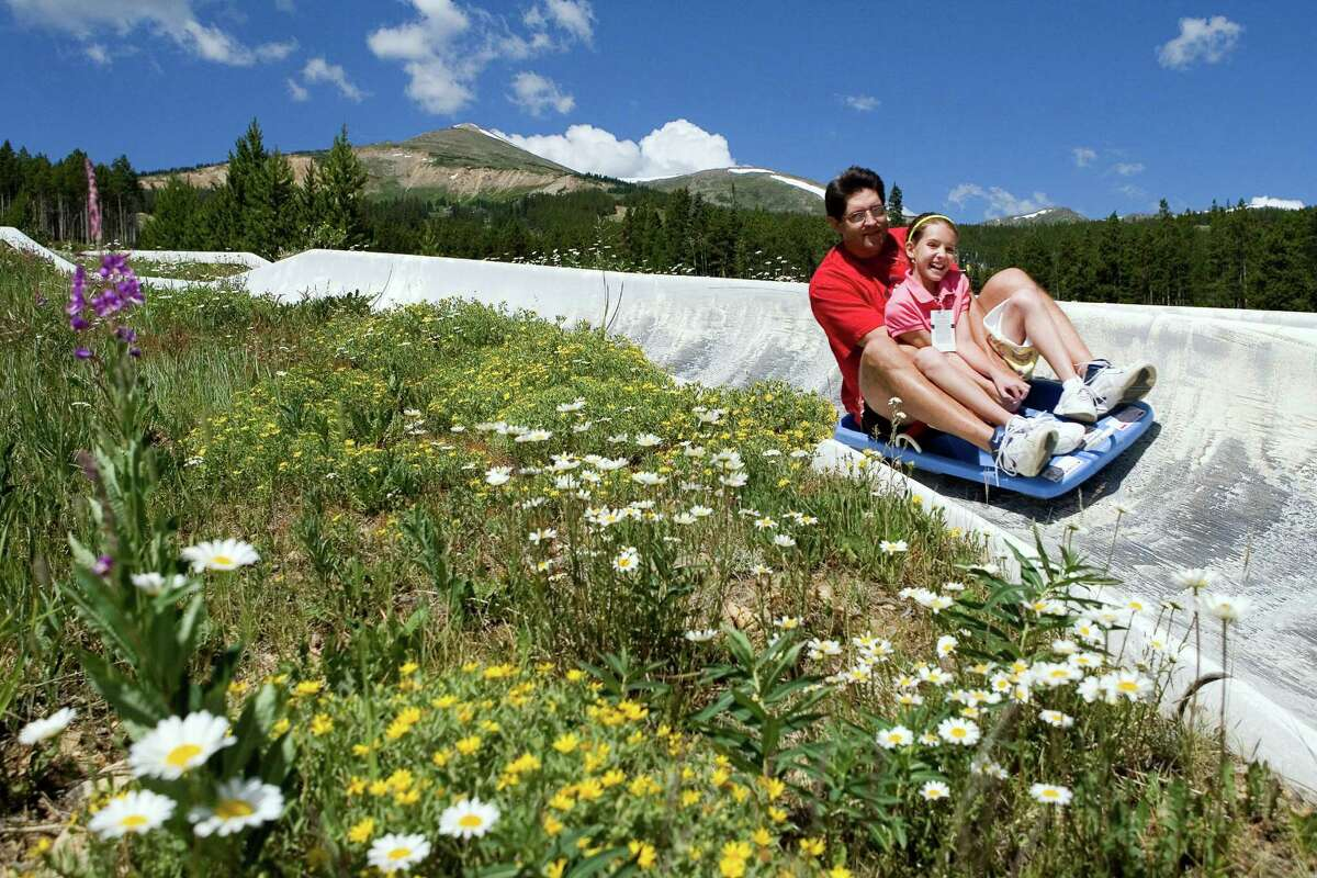 This photo provided by Breckenridge Ski Resort shows visitors enjoying the Alpine SuperSlide in summer at the Breckenridge Fun Park, located at the Peak 8 base area of Breckenridge Ski Resort, in Breckenridge, Colo. Summer's not really the off-season anymore at many ski resorts, which have taken to offering ziplines, ropes courses, disc golf, climbing walls, guided hikes and more.