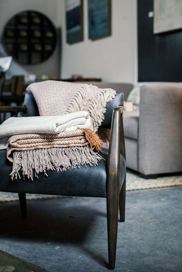 Cozy throws on a chair inside Maker & Moss are emblematic of hygge. Photo: Joshua Harding, Special To The Chronicle